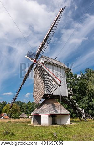 Genk, Belgium - August 11, 2021: Domein Bokrijk. Gray Windmill Of Mol-millegem Under Blue Cloudscape