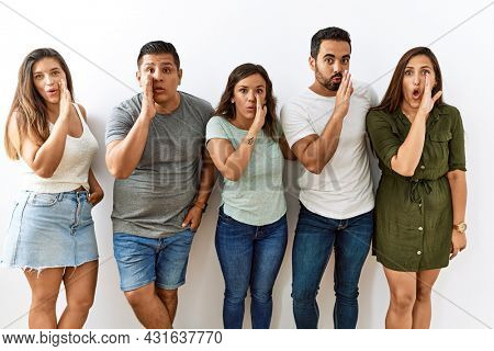 Group of young hispanic friends standing together over isolated background hand on mouth telling secret rumor, whispering malicious talk conversation