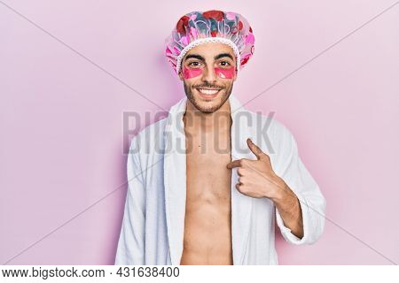 Young hispanic man wearing bathrobe and shower cap using eyes bags patches pointing finger to one self smiling happy and proud