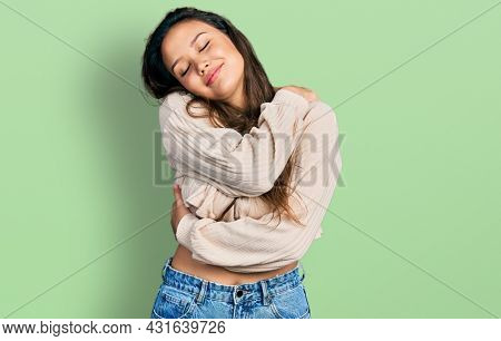Young hispanic girl wearing casual clothes hugging oneself happy and positive, smiling confident. self love and self care