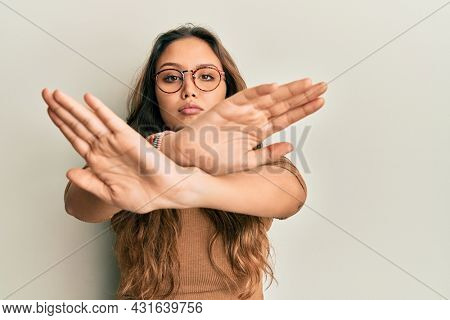 Young hispanic girl wearing casual clothes and glasses rejection expression crossing arms and palms doing negative sign, angry face