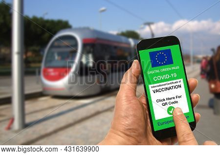 A Man At A Tram Stop Holds A Smartphone With The European Union Digital Green Pass For Covid-19 In H