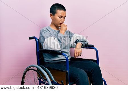 Beautiful hispanic woman with short hair sitting on wheelchair feeling unwell and coughing as symptom for cold or bronchitis. health care concept.