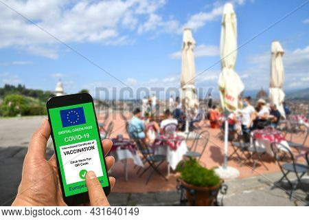 A Man At An Open-air Restaurant Bar Is Holding A Smartphone With The European Union Digital Green Pa