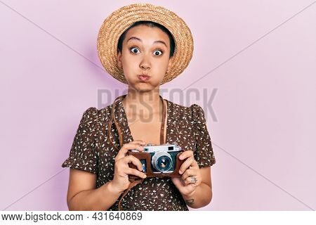 Beautiful hispanic woman with short hair wearing summer hat holding vintage camera puffing cheeks with funny face. mouth inflated with air, catching air.
