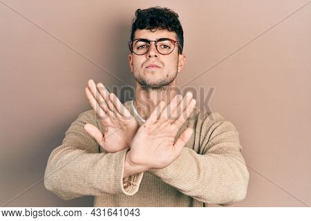 Young hispanic man wearing casual clothes and glasses rejection expression crossing arms doing negative sign, angry face