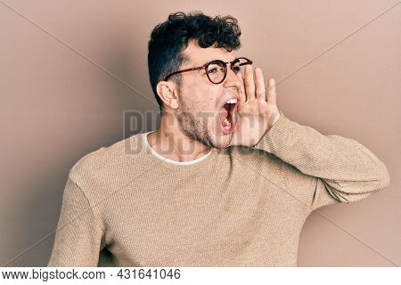 Young hispanic man wearing casual clothes and glasses shouting and screaming loud to side with hand on mouth. communication concept.