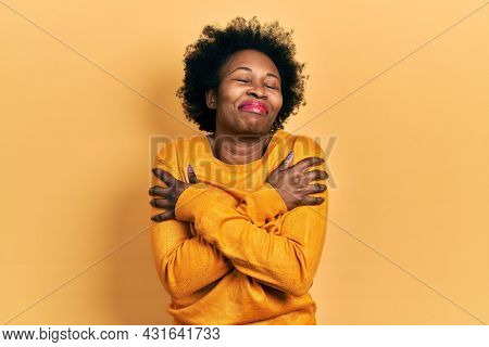 Young african american woman wearing casual clothes hugging oneself happy and positive, smiling confident. self love and self care
