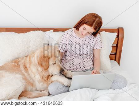 Beautiful teenager red hair girl staying in the bed with laptop in the morning and looking at golden retriever dog lying close to her and holding head at owner legs. Young female person and pet