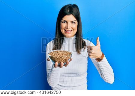 Young hispanic woman holding lentils bowl smiling happy and positive, thumb up doing excellent and approval sign