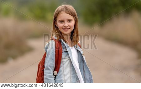 School girl with backpack looking at camera in the field with sunlight. Portrait of preteen child kid at nature