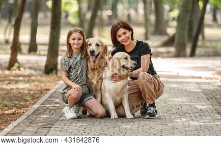 Mother and daughter with golden retriever dogs in the park. Family with pets doggies and preteen girl child outdoors