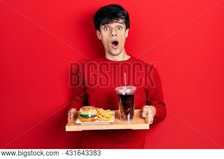 Handsome hipster young man eating a tasty classic burger with fries and soda afraid and shocked with surprise and amazed expression, fear and excited face.