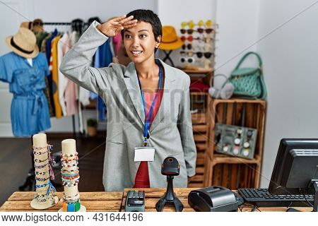 Young hispanic woman with short hair working as manager at retail boutique very happy and smiling looking far away with hand over head. searching concept.