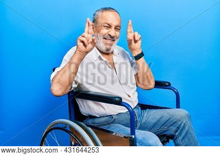 Handsome senior man with beard sitting on wheelchair gesturing finger crossed smiling with hope and eyes closed. luck and superstitious concept.