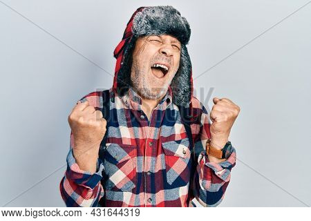 Handsome mature man wearing winter hat with ear flaps crazy and mad shouting and yelling with aggressive expression and arms raised. frustration concept.