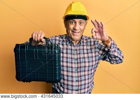 Handsome senior man with grey hair wearing safety helmet holding toolbox doing ok sign with fingers, smiling friendly gesturing excellent symbol