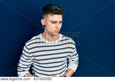 Young caucasian boy with ears dilation wearing casual striped shirt with hand on stomach because indigestion, painful illness feeling unwell. ache concept.