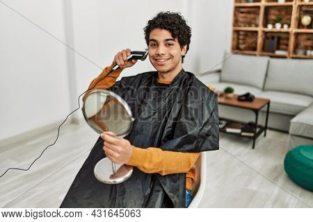 Young hispanic man cutting beard himself at home.