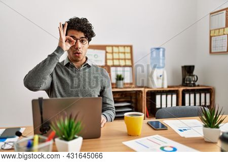 Young hispanic man wearing business style sitting on desk at office doing ok gesture shocked with surprised face, eye looking through fingers. unbelieving expression.
