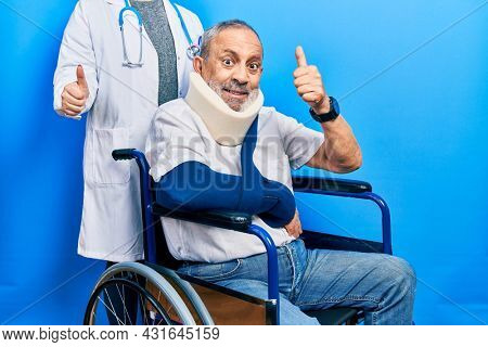 Handsome senior man with beard sitting on wheelchair with neck collar approving doing positive gesture with hand, thumbs up smiling and happy for success. winner gesture.
