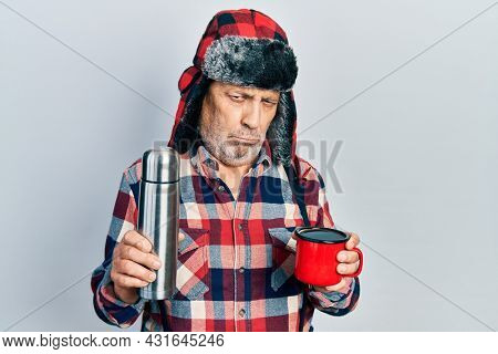 Handsome mature handyman wearing winter hat with ear flaps drinking hot coffee from thermo depressed and worry for distress, crying angry and afraid. sad expression.