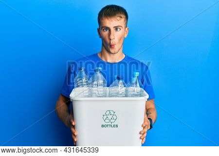 Young caucasian man holding recycling wastebasket with plastic bottles making fish face with mouth and squinting eyes, crazy and comical.
