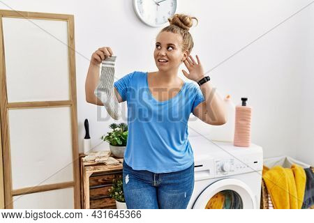 Young caucasian woman holding dirty sock at laundry room smiling with hand over ear listening an hearing to rumor or gossip. deafness concept.