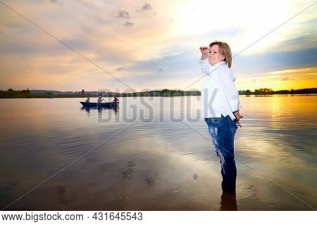 Portrait Of Middle-aged Woman Near Lake Or River During Beautiful Sunset With Sun Above The Horizon