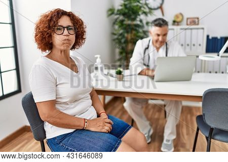 Senior woman sitting at doctor appointment puffing cheeks with funny face. mouth inflated with air, crazy expression.