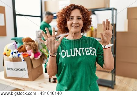 Middle age woman wearing volunteer t shirt at donations stand showing and pointing up with fingers number ten while smiling confident and happy.