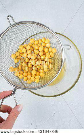 Chickpea Water Aquafaba. Egg Replacement. Vegan Concept. Metal Sieve Draining Aquafaba Chickpea Wate