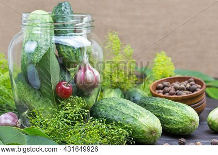 Garlic, Cucumbers And Cherries In Glass Jar. Cucumbers And Dill On Table. Homemade Fermentation Prod