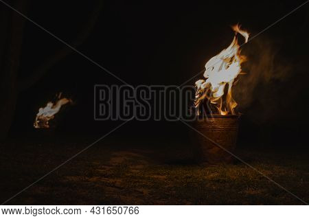 Burning Firewood In Iron Pail For Heating. Wood Burns In A Metal Buckets To Protect Trees From Freez