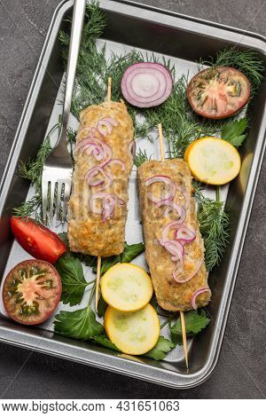 Ready-to-eat Meat Kebab With Vegetables And Herbs In Tray. Black Background. Flat Lay