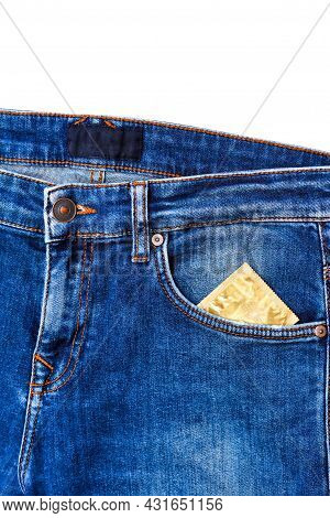 Condom Packaging In The Side Pocket Of Blue Men's Jeans. Closed Fly On A Pair Of Jeans And Condom Pa