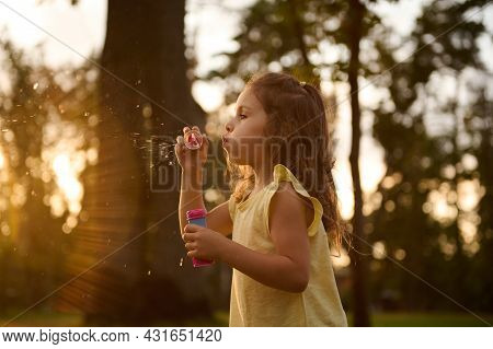 Beautiful Gorgeous Cute Adorable Little Girl Blowing Soap Bubbles At Sunset. Carefree Childhood, Out