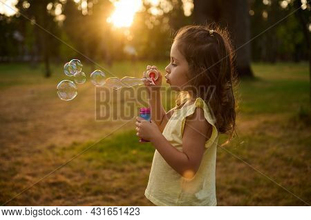 Adorable Beautiful Child Baby Girl, Blowing Soap Bubbles At Sunset, Enjoying Pleasant Time Outdoors
