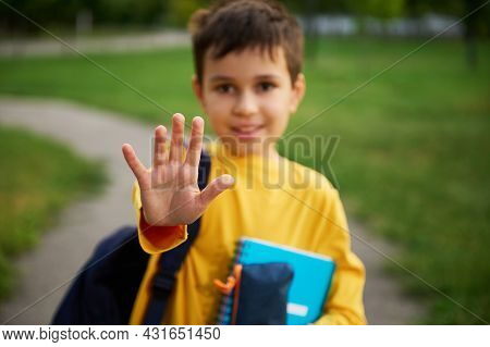 Out Of Focus Adorable Schoolboy Showing Stop With His Hand, Standing With Backpack And School Suppli