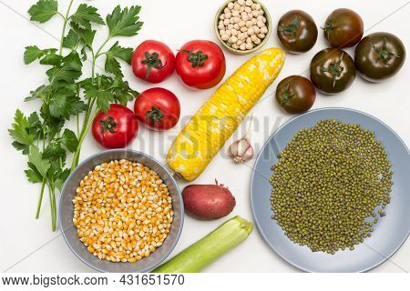 Chickpea, Corn And Mung Bean Grains In Plates. Swing Of Yellow Corn, Tomatoes And Parsley Sprigs On