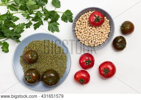 Chickpea Grains And Mung Bean In Gray Plate. Tomatoes And Sprigs Of Parsley On Table. White Backgrou