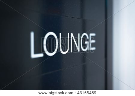 Black sign to lounge room in airport.