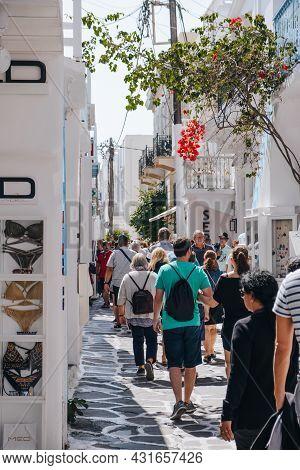 Mykonos Town, Greece - September 23, 2019: Rear View Of People Walking Past Shops On A Narrow Street