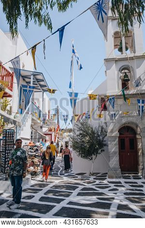 Mykonos Town, Greece - September 24, 2019: People Walking Under Colourful Bunting On A Narrow Street