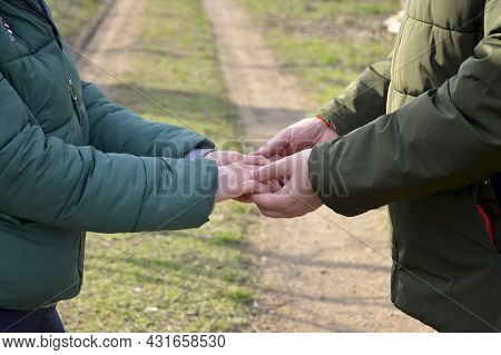 A Man And A Woman Stand Opposite Each Other And Hold Hands, The Girl Put Her Hands In The Man's. Lov