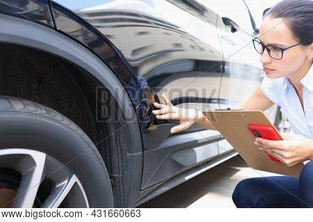 Insurance Agent Filling Out Insurance Form Near Damaged Black Car