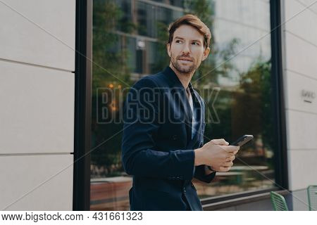 Pensive Young Businessman In Dark Suit Holding Smartphone, Thinking About How To Reply To Partner, L