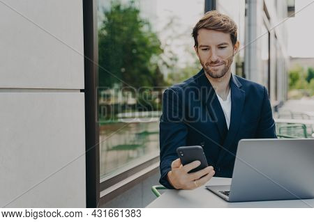 Focused Young Businessman Working On Laptop Remotely, Browsing Phone Notifications While Drinking Co