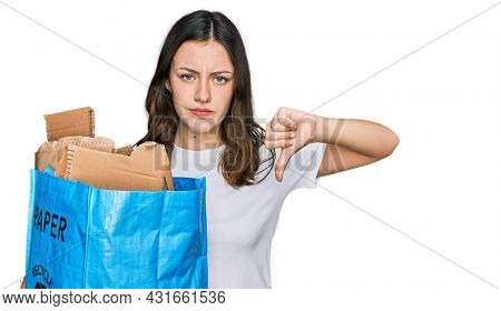 Young beautiful woman holding recycling wastebasket with paper and cardboard with angry face, negative sign showing dislike with thumbs down, rejection concept