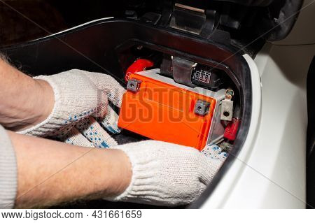 Replacing The Motorcycle Battery. An Auto Mechanic In A Car Service Takes The Battery Out Of The Mot